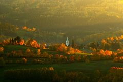 Evening in Kasperske hory church, Sumava, Czech Republic. Cold day in Sumava National park, hills and villages in orange trees, mi Royalty Free Stock Image