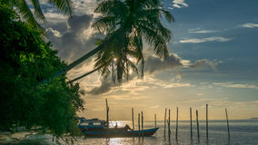 Evening on Kri Island. Boats under Palmtrees. Raja Ampat, Indonesia, West Papua. Evening on Kri Island. Boats are laying under Palmtrees. Raja Ampat, Indonesia Royalty Free Stock Images