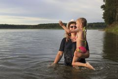 Evening, lake. The child in the arms of his mother is in the lake. stock photo
