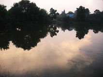 Evening on a lake. Evening sky and rural house are reflected in a lake Royalty Free Stock Images