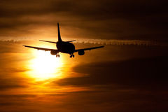 Evening landing. Silhouette of airplane landing during sunset Stock Photography