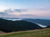 Evening landscape of Carpathians mountains at summer, west Ukraine. Hillsides covered with dense forest. Low clouds. Flowing between high peaks. Ukrainian royalty free stock images