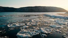 Evening landscape of a freezing river. The ice floats near the shore, but the current does not allow to freeze the
