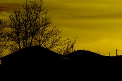 Evening landscape immediately after sunset. Silhouettes of houses and tree against the sky royalty free stock photography