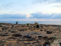 Evening sky above the coast of Cyprus. Evening landscape of the island of Cyprus in the Paphos area. The shore seems to be laid out with ancient stones stock photo