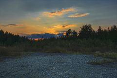 Evening landscape meadow against the backdrop of the forest at sunset stock photography