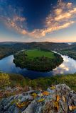 Evening landscape with river. Big Czech horse shoe meander, green vegetation with evening sun. River Vltava with white clouds. Eve. Evening landscape with river royalty free stock photo