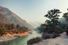 Evening landscape with a river. Mountains and a bridge. India, Rishikesh Stock Photos