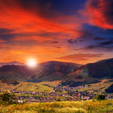 Evening light  beam falls on hillside with autumn village in mou Stock Images