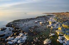 Evening light colors by a flat rock coast Stock Photo