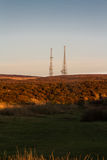 Evening light on hilltop with radio masts Royalty Free Stock Photo