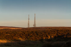 Evening light on hilltop with radio masts Royalty Free Stock Photos