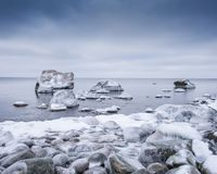 Evening light and icy weather on shore like fairy tale country. Rocky beach on wintertime. Evening light and icy weather on shore like fairy tale country Stock Photo