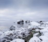 Evening light and icy weather on shore like fairy tale country. Rocky beach on wintertime. Evening light and icy weather on shore like fairy tale country Stock Photography