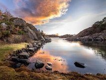 Evening light, ocean, stones and rocks by the seaside, warm light and sunset in the background. Autumn. Randesund in Kristiansand, Norway royalty free stock photos