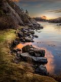 Evening light, ocean, stones and rocks by the seaside, warm light and sunset in the background. Autumn. Randesund in Kristiansand, Norway. Vertical image royalty free stock photos