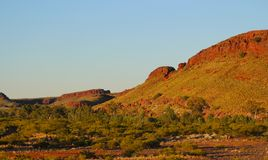 Evening light on red rocks, South Australia. The sun sets beyond hills at the edge of a lake in Northern Australia Stock Photography