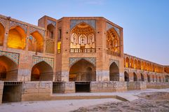 Safavid era bridge in Isfahan, Iran. The evening lights decorated the outstanding Khaju bridge with its multiple arches, tiled and painted patterns, inner royalty free stock image