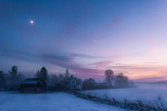 Evening lights. Enchanting winter scenery at sunset, showing a few houses and the moon royalty free stock photos