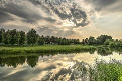 Evening at the little river. Dramatic evening skies reflecting in the calm water of Koedood river on the island of IJsselmonde, just south of Rotterdam Royalty Free Stock Image