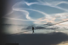 Evening Loneliness. A lone black drongo sitting on a wire in the backdrop of beautiful clouds after rocket launch Stock Photo
