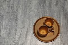 Valentine`s Day. Brown ceramic coffee cups tied with jute twine on ceramic platter. Dark concrete background. royalty free stock image