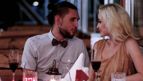 Evening for lovers, loving couple in the restaurant, Valentine`s Day, romantic date, boys and girls in a romantic. Atmosphere in the cafe, beautiful table stock video footage
