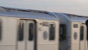 Evening lower Manhattan skyline as subway car passes. An evening skyline establishing shot of Lower Manhattan as a Queens-bound elevated subway car passes by stock footage