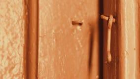 In the evening, a man`s hand opens a wooden door in a house locked on a hook. Incandescent lighting. The wooden door is painted. Beige. Dark doorway. Primitive stock footage