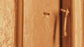 In the evening, a man`s hand opens a wooden door in a house locked on a hook. Incandescent lighting. The wooden door is painted. Beige. Dark doorway. Primitive stock video footage