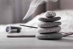 Free Evening Meditation At Home. Pyramid Of Zen Stones, Burning Incense Stick Next To Watch Lying On White Wooden Table In Royalty Free Stock Photography - 164825667