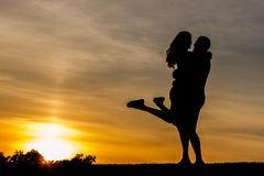 Evening meeting of lovers outdoors. Vening meeting of lovers outdoors. Guy hugs the girl on a background of the evening sky. Romantic date in the mountains Stock Photos