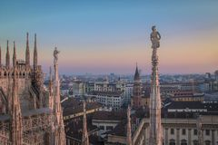 Evening Milan, view of the city from the terrace of the Duomo. Statues and decorative elements on the roof of the Duomo. Evening Milan, view of the city from the stock image