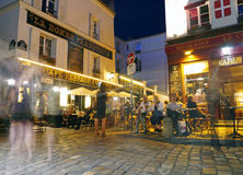 An evening in Montmartre - cafe culture on a Paris evening. A long exposure of the beautiful, picturesque Montmartre restaurants, cafes and brasseries in the Stock Photos