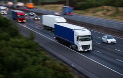 Evening motorway traffic. Lorries in motion. Evening traffic on the motorway royalty free stock photo