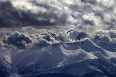 Evening mountain with clouds and silhouette of parachutist Stock Images