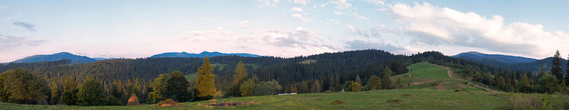 Evening mountain panorama. Summer evening twilight panorama view with green pasture meadow and ultramarine color distant ridge (Slavske village outskirts Stock Photography