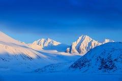 Evening mountain. White snowy mountain peak, blue glacier Svalbard, Norway. Ice in ocean. Iceberg in North pole. Beautiful landsca Stock Photography