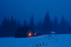 Evening in mountains. High-mountainous small house in the Ukrainian Carpathians. Winter evening, on a cross with Jesus burns a candle royalty free stock photos
