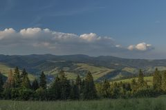 Evening in national park Pieniny with sunny shine over green meadows. And blue sky over heads stock photography