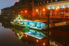 Evening and night sketches on the millet streets in the center of the port of Hamburg. The muffled light makes its way through an easy fog. Reflections of the Royalty Free Stock Photo