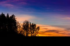 Evening orange sunset over field and forest. Royalty Free Stock Photos