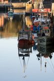 Evening light n boats in Padstow harbour. Evening at Padstow harbour as fishing boats are moored on calm still water stock images