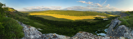 Evening panorama of the green valley. View from the top of cave city Bakla in Crimea. Royalty Free Stock Photo
