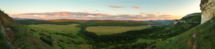 Evening panorama of the green valley. View from the top of cave city Bakla in Crimea. Stock Image