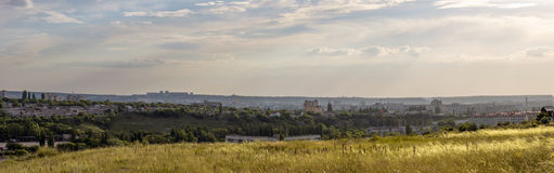 Evening panoramic landscape with field, sky, clouds and city in. The distance Stock Photography