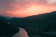 Evening panoramic view of Mtskheta city and Kura river from Jvari monastery at sunset. Georgia Stock Photo