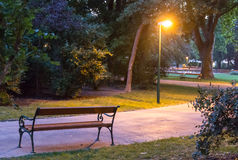 Evening park alley. Scenery with empty bench Stock Photography