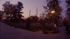 Evening park and a mosque with minarets, the silhouette of a motorcyclist rides along the road. KONYA / TURKEY - 11.20.2016 central streets of the ancient stock video footage