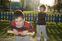 In the evening in the park on the playground boy riding on a swi Stock Photography